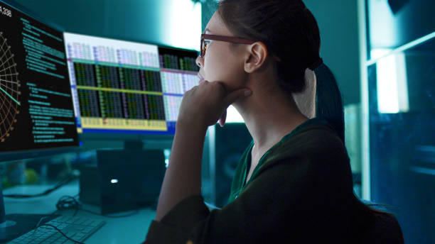 monitors asian woman Stock photo of an Asian woman surrounded by computer monitors in a dark room crime stock pictures, royalty-free photos & images