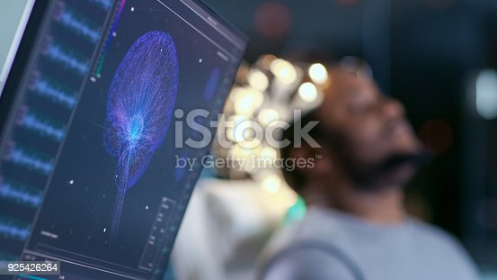istock Monitors Show EEG Reading and Graphical Brain Model. In the Background Laboratory Man Wearing Brainwave Scanning Headset Sits in a Chair with Closed Eyes. In the Modern Brain Study Research Laboratory 925426264