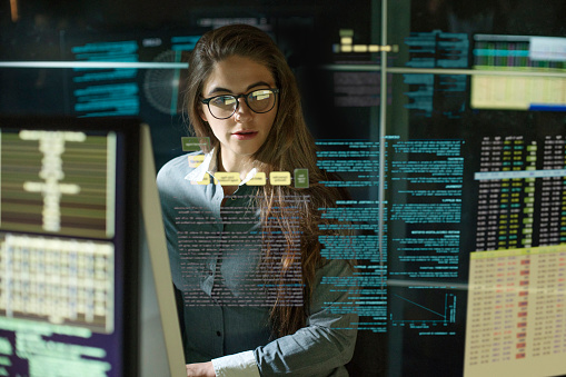 Stock photo of a young woman working in a dark research environment looking at data on virtual & real computer monitors with some see through text.