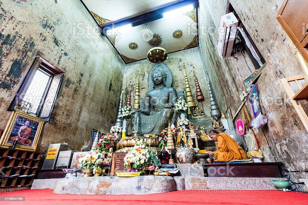 Monk and Ancient Buddha Statue in Wat Nah Phramen Chapel stock photo