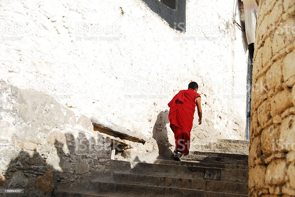 Monk climbing the stairs stock photo