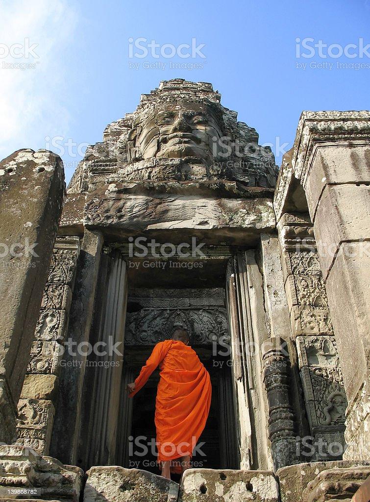 Monk enters Bayon Temple at Angkor Thom, Cambodia royalty-free stock photo