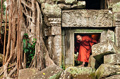 Cambodian monk ducks under a short doorway to explore an ancient temple with fallen stones and tangled roots encroaching the structure, Ta Prohm, Angkor Wat, Siem Reap, Cambodia, Asia