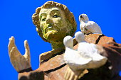 Monk friar blessing with doves in cemetery