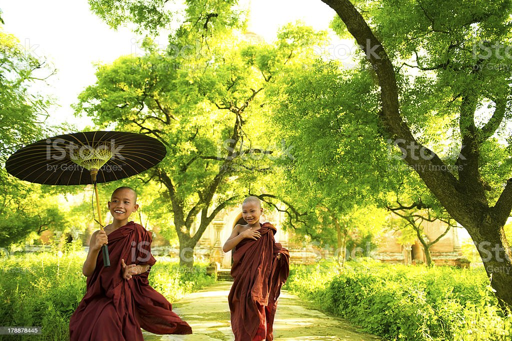 A monk holding a traditional umbrella stock photo