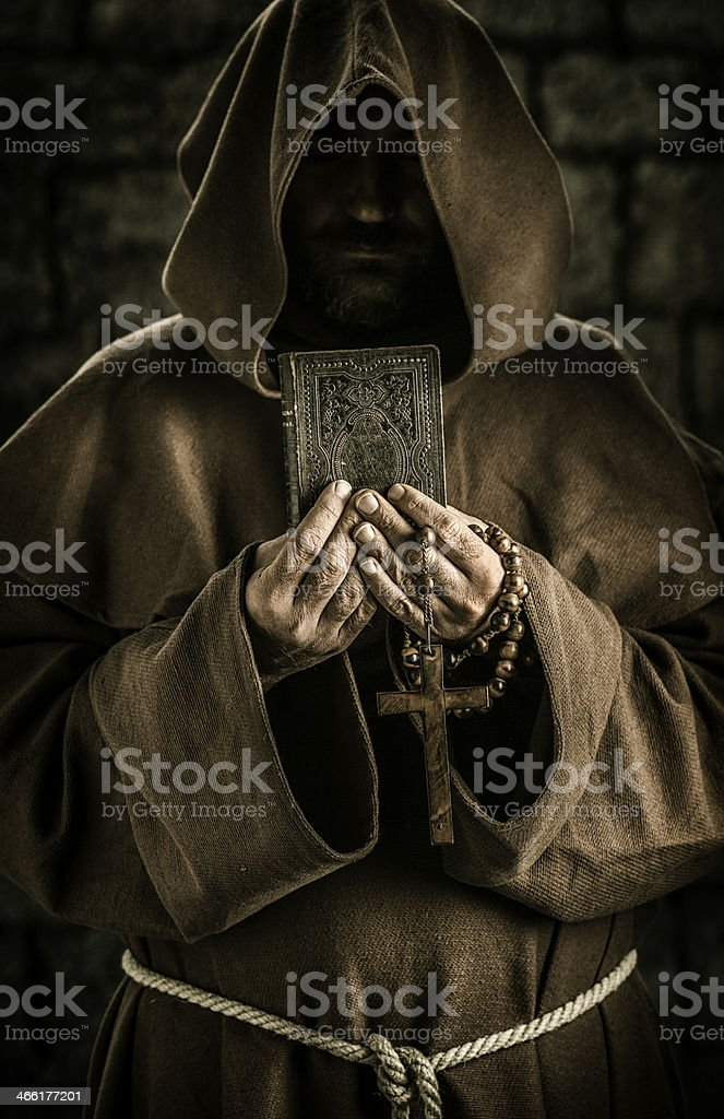 Monk holding book and rosary stock photo