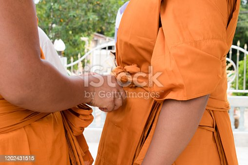 Monk is covering the cloth. Thailand.