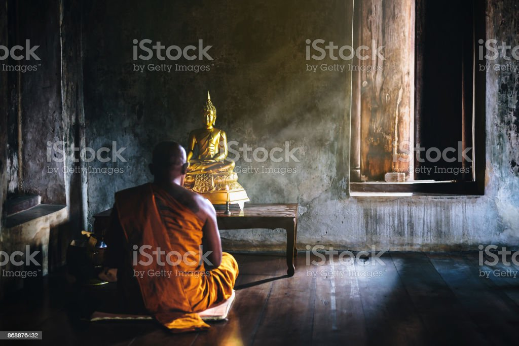 A monk is worshiping and meditating in front of the golden Buddha as...