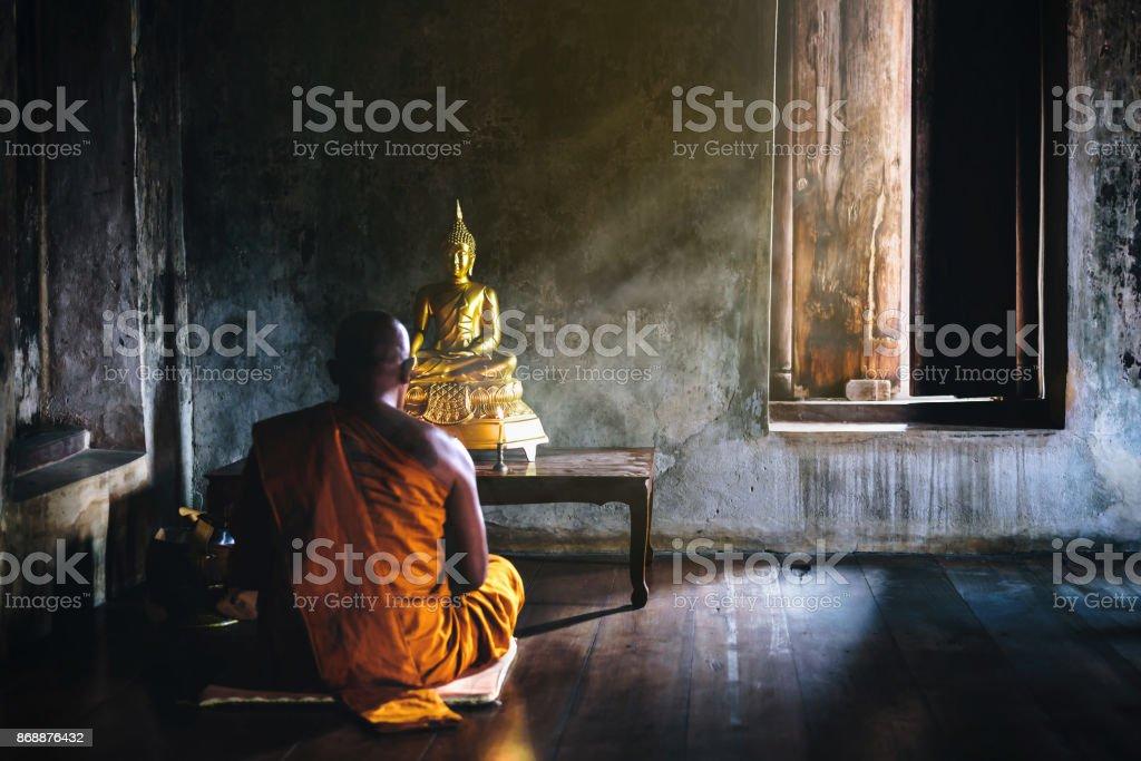 Een monnik is aanbidden en mediteren voor de Gouden Boeddha als onderdeel van de boeddhistische activiteiten. Focus op de Boeddha foto