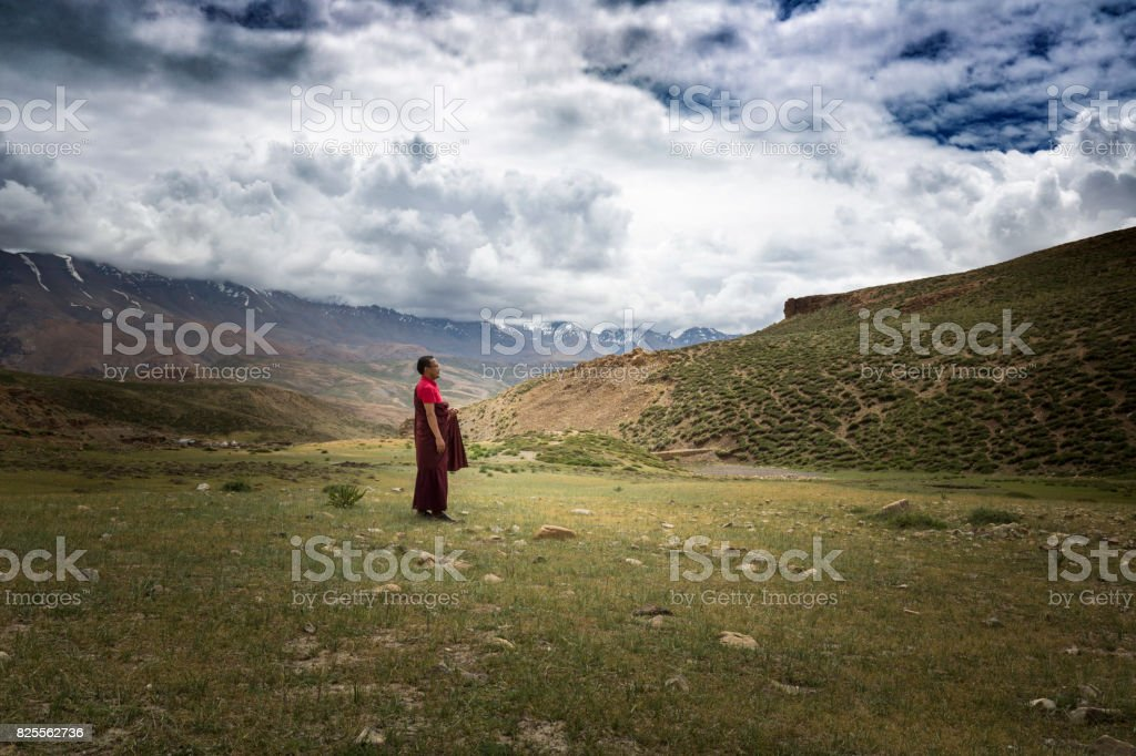 monk meditating alone in a valley stock photo