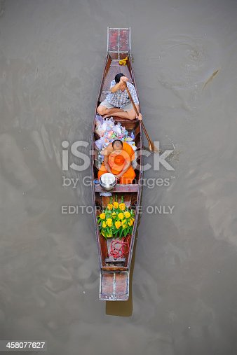 Samudsongkarm, Thailand - September 27, 2009: Monk rows a boat to receive food in the morning at Amphawa floating market in Samudsongkarm, Thailand.