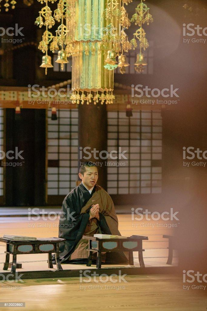 Monge rezando durante a cerimônia de manhã dentro de um templo budista - foto de acervo