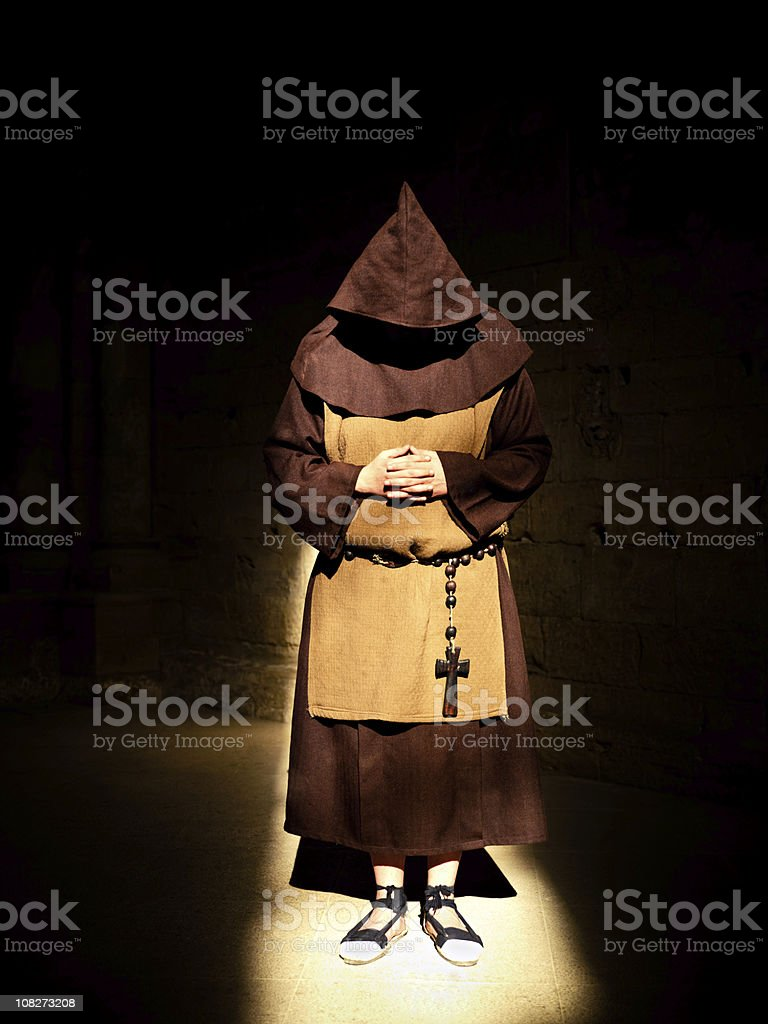 Monk Praying in the Shadows royalty-free stock photo