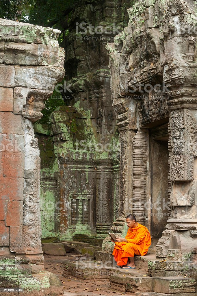 Monk reading at ruins stock photo