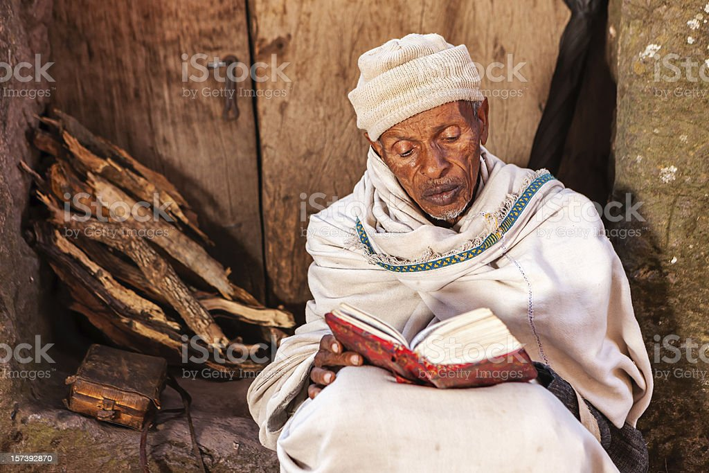 Monk reading the holy book near one of Lalibela's churches stock photo