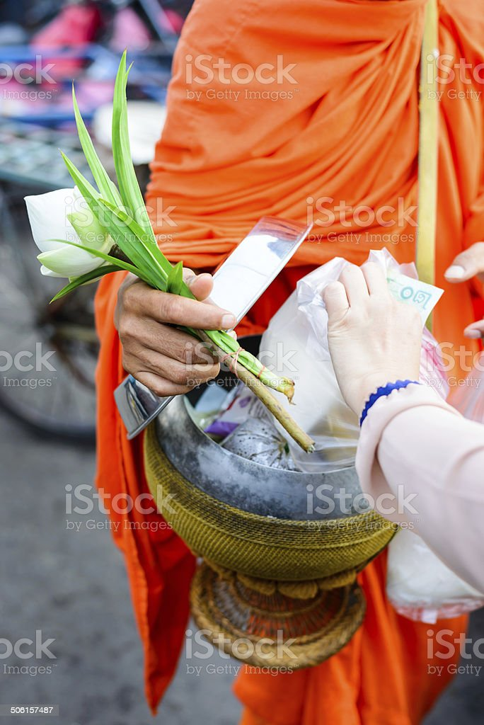 Monk receiving food and items offering from people stock photo