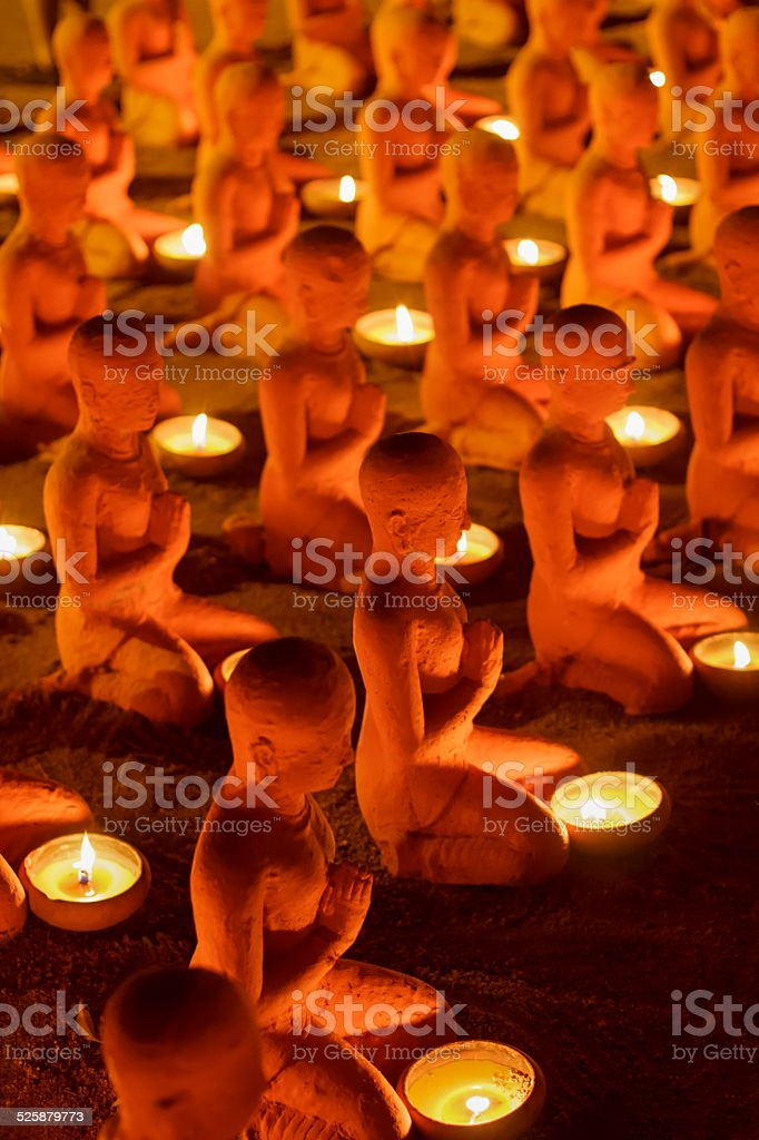 Monk sculptures with candles at temple in buddhist holy day stock photo