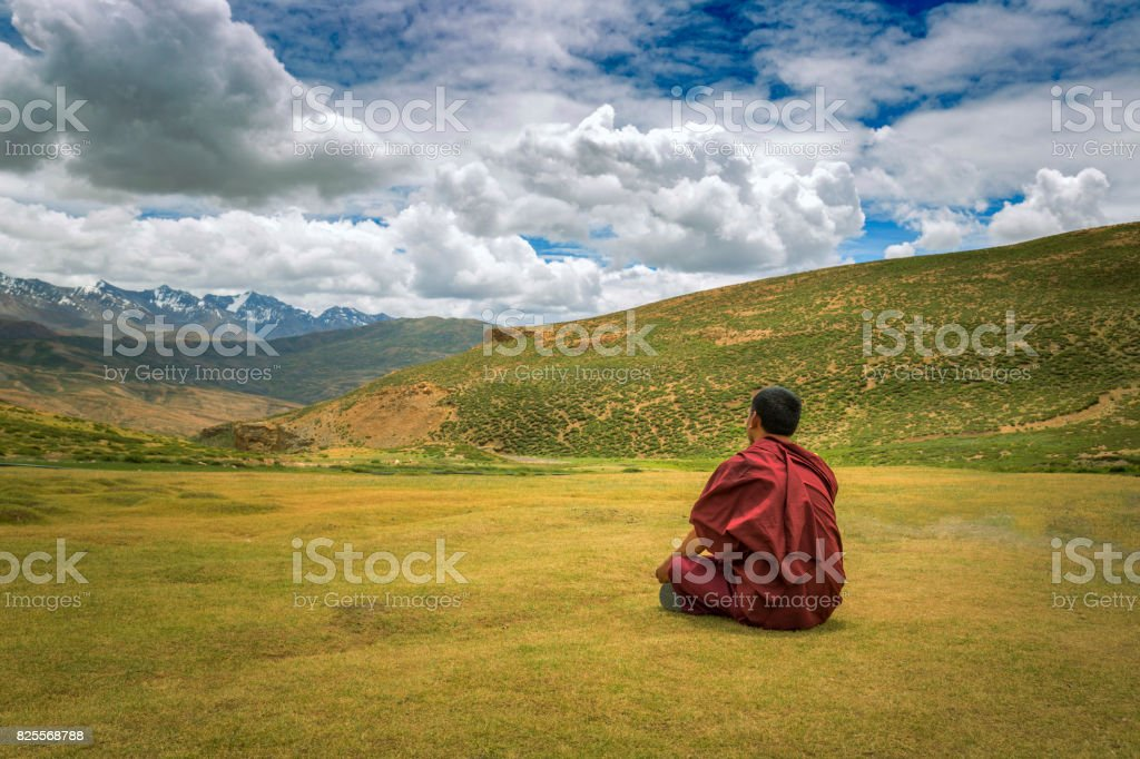 monk sitting  alone on ground in a valley stock photo