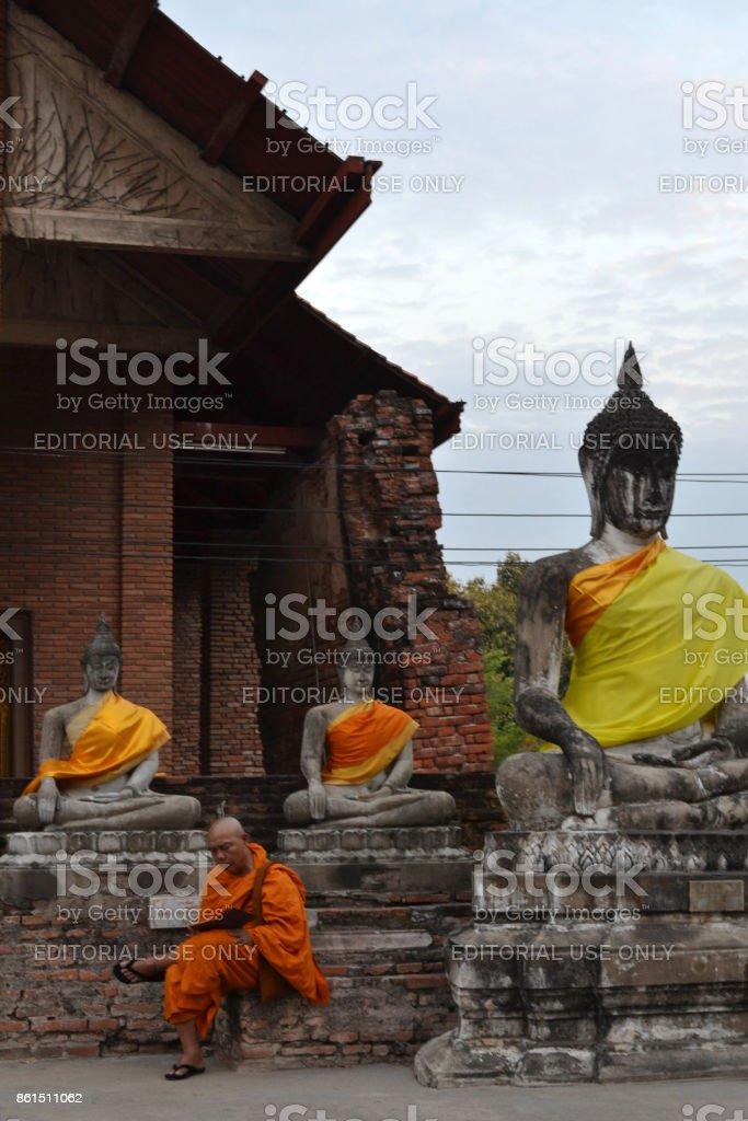 A monk sitting around Ayutthaya Historical park, Thailand stock photo