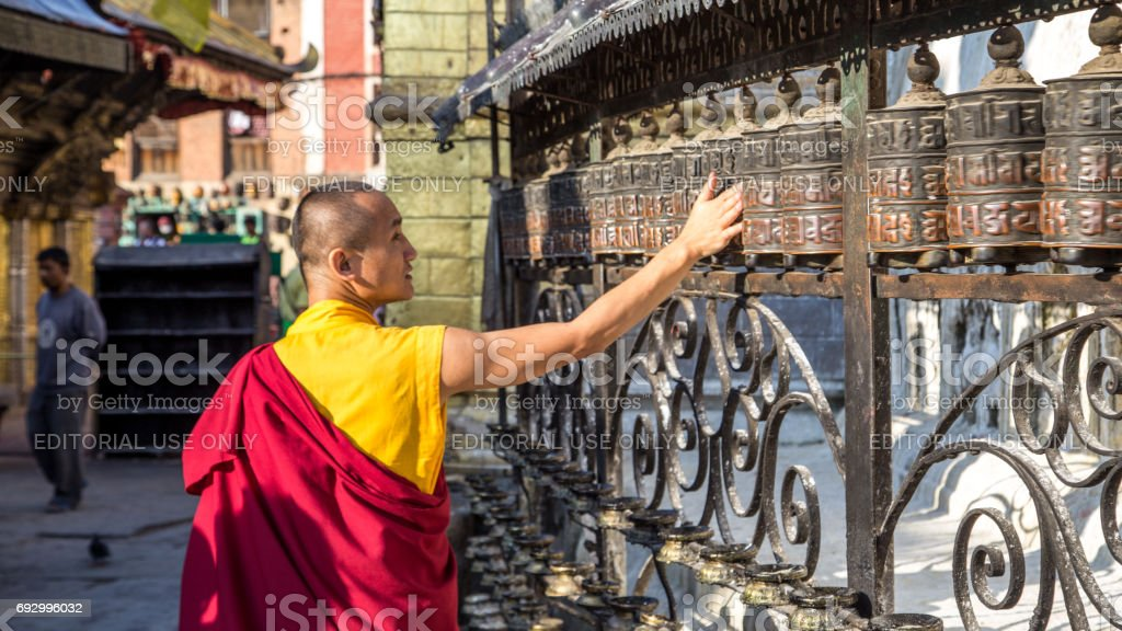 Monk spinning prayer wheels stock photo