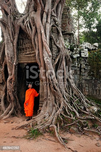 A monk in an orange robe touches the doorway of an ancient temple surrounded by tangled roots of tree growing around temple doorway; Ta Prohm temple, Siem Reap, Cambodia