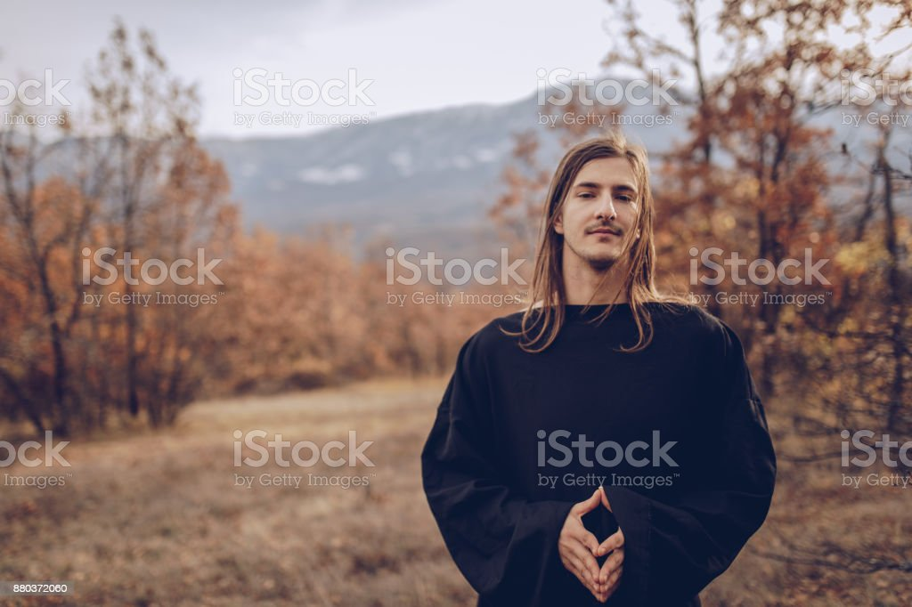 Monk standing in the woods stock photo
