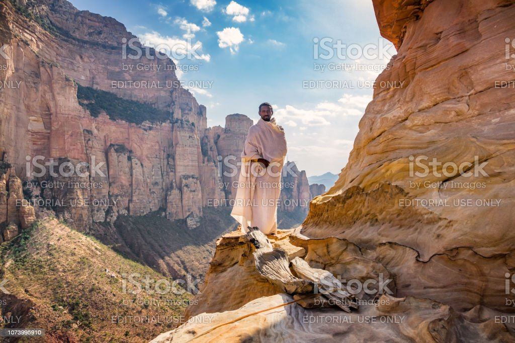 Monk stands at Abuna Yemata Guh monolithic church in Hawzen Tigray region Ethiopia stock photo