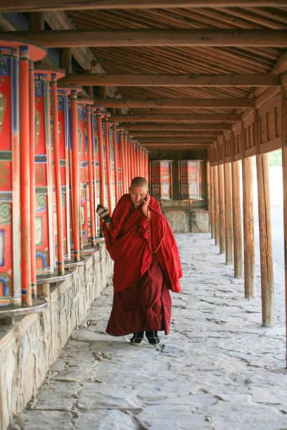 Monje girar las ruedas de oración mientras que en el teléfono en el monasterio del budista de Labrang, China - foto de stock
