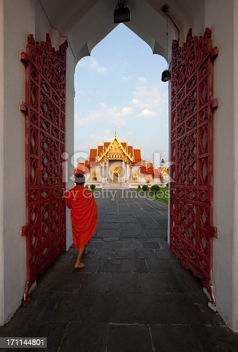 Buddhist monk walking through the entrance gate into the Marble Temple (Wat Benchamabophit), Bangkok, Thailand after collecting alms in the early morning.