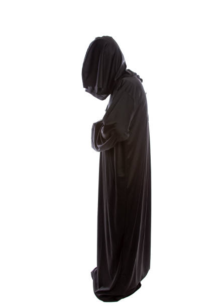 Monk Wearing Black Robes Monk wearing black robes and a hood or a person in a halloween costume of a grim reaper ghost.  The image depicts a priest in traditional or ancient clothing. friar stock pictures, royalty-free photos & images