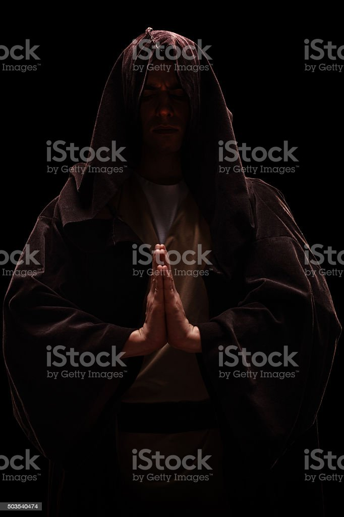 Monk with a hood on his head praying stock photo