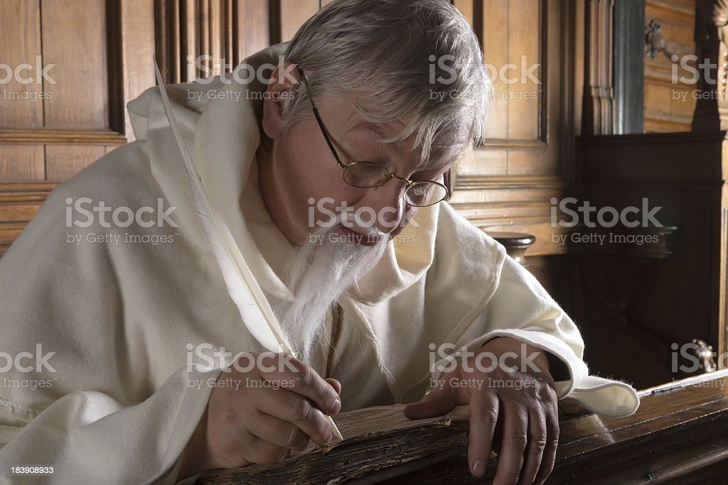 Monk with feather quill stock photo