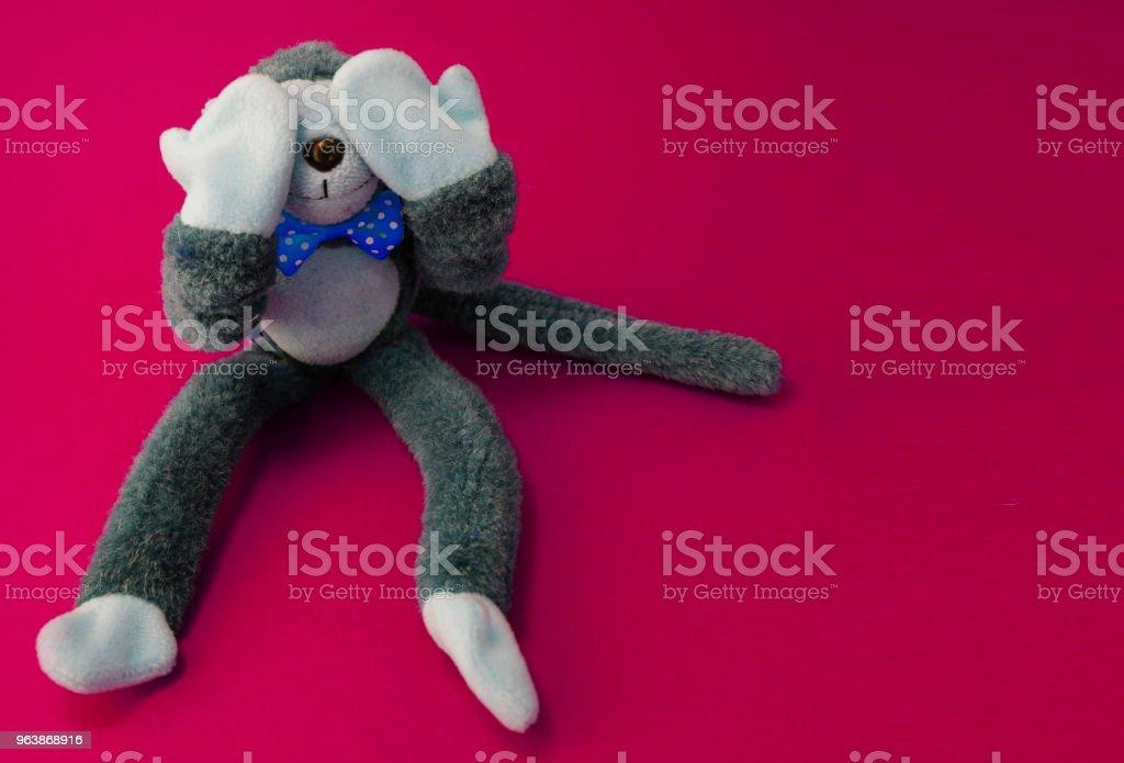 Monkey doll closes eye in maroon background - Royalty-free Animal Stock Photo