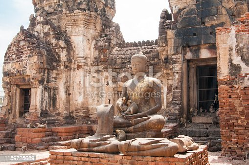 Monkeys sit in the cradled arms of a serene Buddha statue with eyes closed, missing nose, and hands in meditative pose outside a temple ruin with decaying bricks, Lopburi, Thailand, Asia