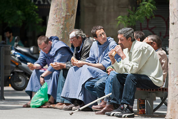 """monks in Barcelona """"Barcelona, Spain; May 17, 2009:monks in the center of barcelona, nearby the cathedral """"""""La Sagrada Familia"""""""" in conversation with poor people and sharing their meal with them"""" friar stock pictures, royalty-free photos & images"""