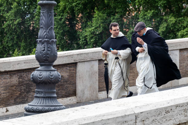 Monks in cassock dress cross a bridge in the historic center of the city during a windy day. Rome, Italy - May 20, 2020: Two monks in cassock of the circestense order cross a bridge in the historic center of the city during a windy day. friar stock pictures, royalty-free photos & images