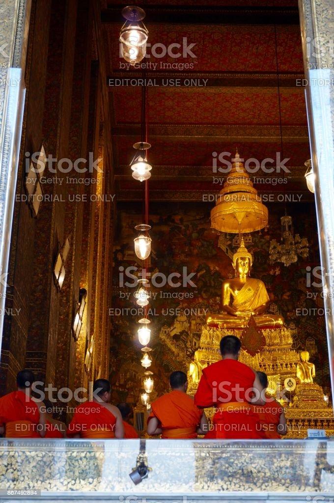 Monks praying at Wat Arun temple in Bangkok stock photo