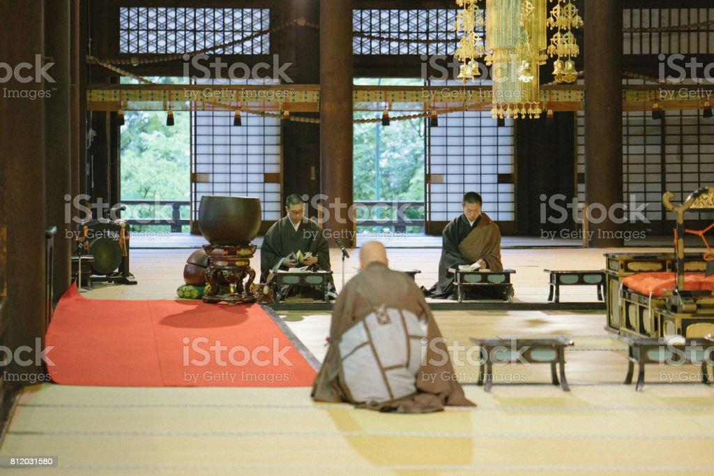 Monges rezando durante a cerimônia de manhã dentro de um templo budista - foto de acervo