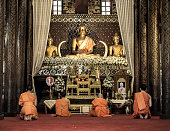 Monks praying in Wat Buppharam Chiang Mai Thailand. Build in 1497 the complex houses temples like the one in the image where a group of monks is praying in front of a large Buddha statue