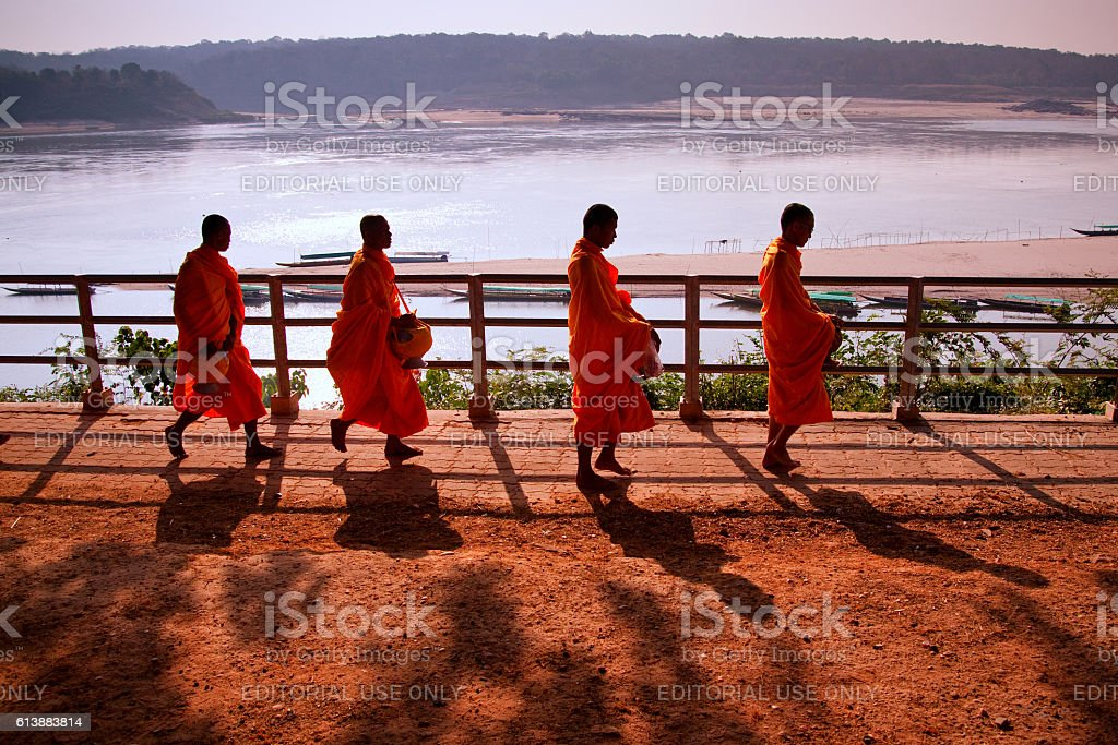 Monks receive alms bowl out to beg for food stock photo