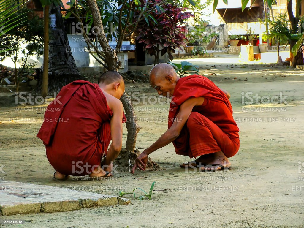 Monks sitting at Shwe In Bin Kyaung monastery, Mandalay, Myanmar stock photo