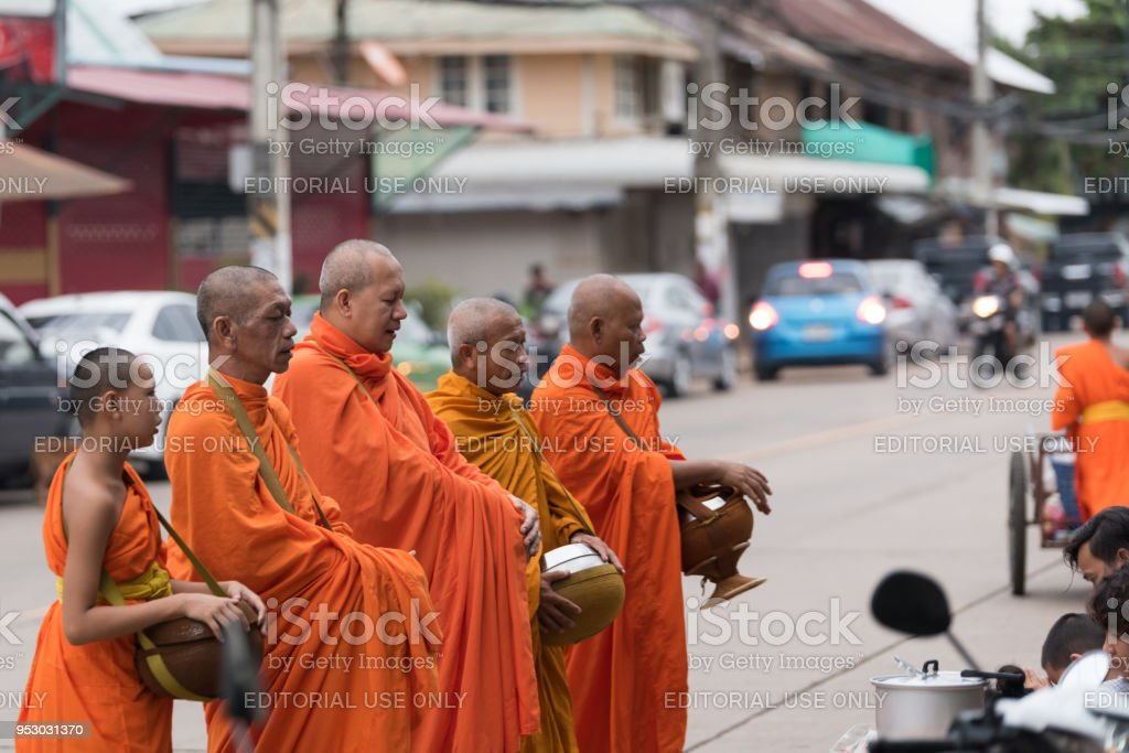 monks walking on the street to collect alms and offerings in the morning (for alms-gathering) for people pray and put food offerings.Thai culture and religion. stock photo