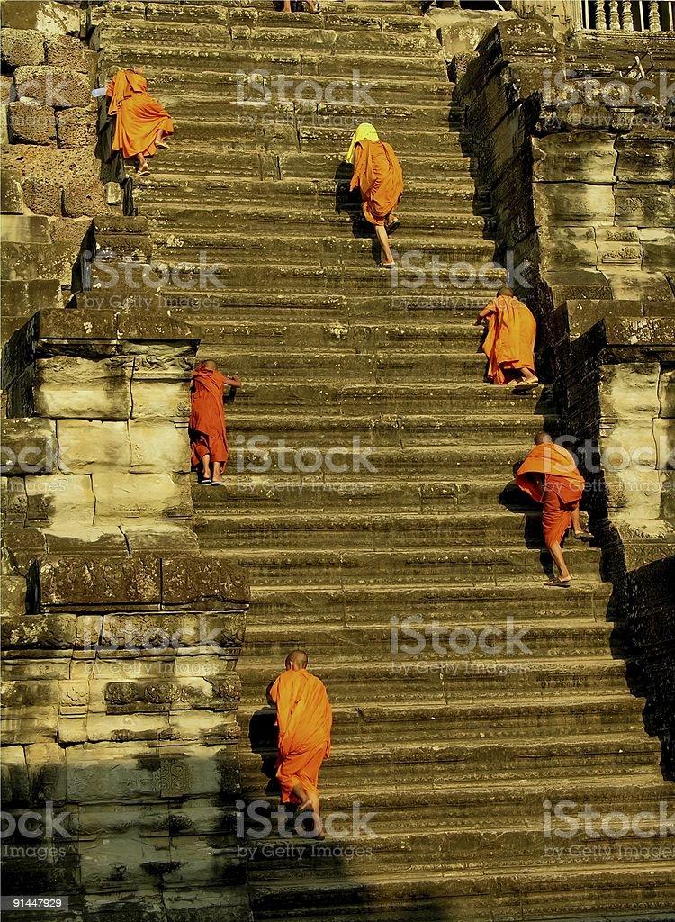 Monks walking upstairs in Angkor royalty-free stock photo
