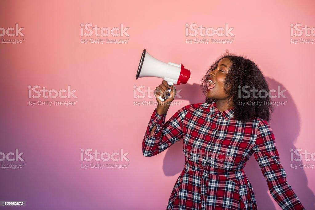 Monochrome - femme noire sur fond rose hurle en mégaphone - Photo