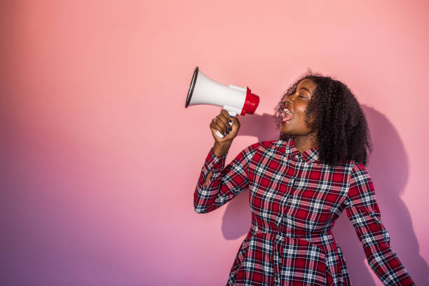 Monochrome -  Black Woman on Pink Background Yells into Megaphone stock photo