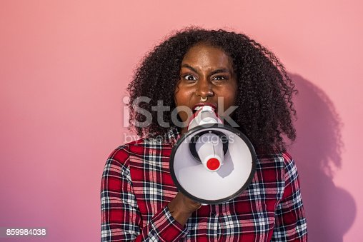 657442382istockphoto Monochrome -  Black Woman on Pink Background Yells into Megaphone 859984038