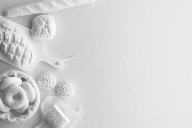 Composition monochrome de la figure blanche de pain, pain long, brioches, produits de boulangerie sur un fond blanc. Bannière avec espace de copie pour le texte. Un ensemble de nourriture sur la vue de dessus. - Photo