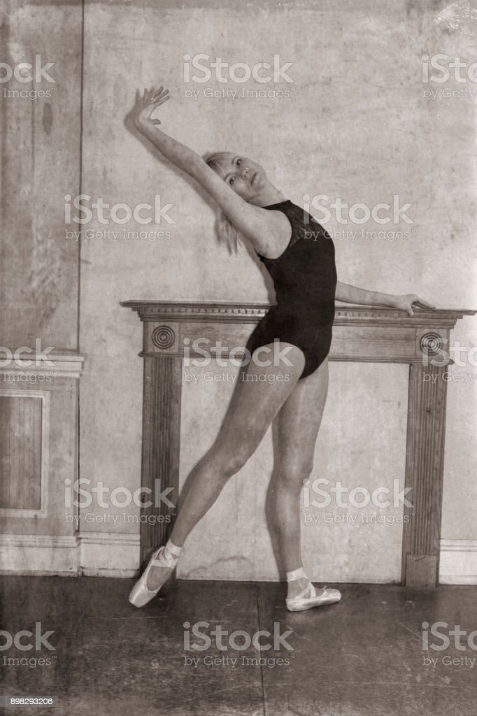 Monochrome Danish ballerina stretching before mantel filled in fireplace stock photo