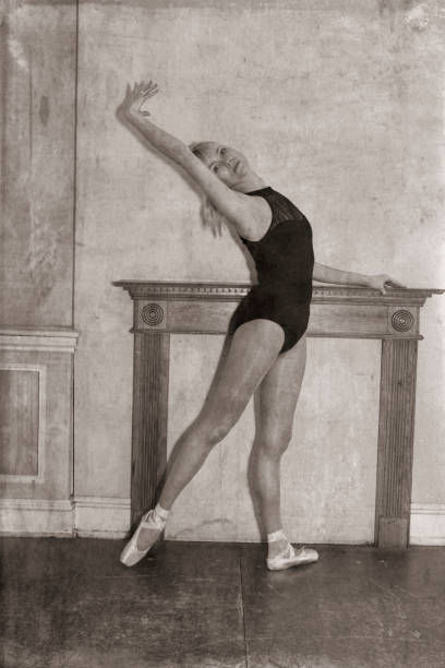 monochrome danish ballerina stretching before mantel filled in fireplace - whiteway danish stock photos and pictures