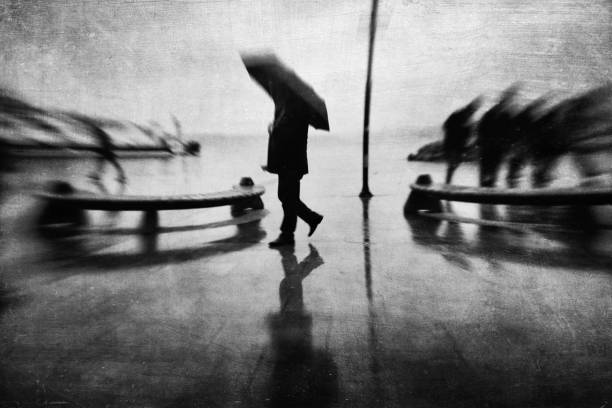 Monochrome defocused view of a man walking with umbrella